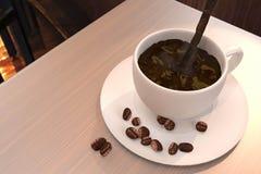 O café preto derrama ao copo de café decora por feijões de café Foto de Stock