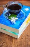 O café preto na tabela com livros velhos e o jasmim florescem Foto de Stock