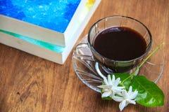 O café preto na tabela com livros velhos e o jasmim florescem Imagens de Stock Royalty Free