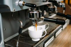 O café que faz a máquina derrama a dose da cafeína dos copos imagens de stock royalty free