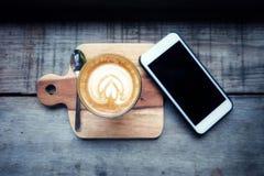 O café quente do latte é colocado em uma bandeja de madeira Com smartphone foto de stock royalty free