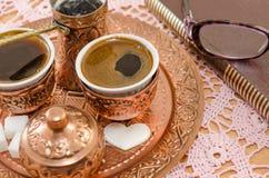 O café serviu na cerâmica de cobre e em um livro Imagens de Stock