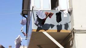 O cair das coisas e torna-se no balcão As coisas secam em cordas sob o sol da cidade Os homens lavados vestem seco na corda no video estoque