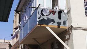 O cair das coisas e torna-se no balcão As coisas secam em cordas sob o sol da cidade Os homens lavados vestem seco na corda no vídeos de arquivo