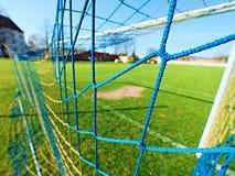 O cair dobrou redes amarelas azuis do futebol, rede do futebol do futebol Grama no campo de jogos do futebol no fundo Fotos de Stock