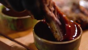 O cair na luva preta do alimento coloca o reforço suculento no fim do molho de tomate filme