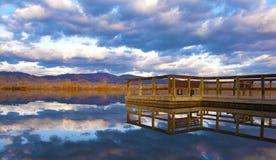 O cais alcanga em um lago tranquilo fotografia de stock