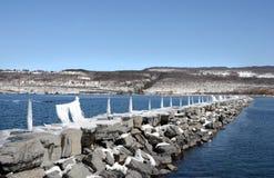 O cais da rocha no inverno projeta-se para fora no porto do lago Imagens de Stock