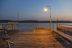 O cais de madeira no lago iluminou-se pela lâmpada Fotografia de Stock Royalty Free