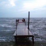 O cais ou o molhe de madeira esticam para fora em um oceano idílico Foto de Stock