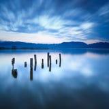 O cais ou o molhe de madeira permanecem em uma reflexão azul do por do sol e do céu do lago na água. Versilia Toscânia, Itália Imagens de Stock