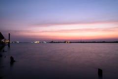 O cais ou o molhe de madeira permanecem na água azul da reflexão do por do sol e do céu do lago Foto de Stock