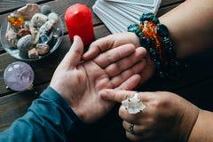 O caixeiro de fortuna da quiromancia lê linhas na mão ou na palma do homem para dizer seu futuro, vista superior imagem de stock royalty free