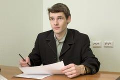 O caixeiro no escritório senta-se em um desktop Foto de Stock Royalty Free