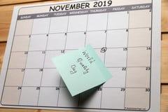 O calendário com uma nota encontra-se em uma tabela de madeira fotografia de stock royalty free
