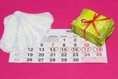 O calendário das mulheres em que a higiene e as almofadas diárias, ginecologia, fundo cor-de-rosa, dias marcados foto de stock
