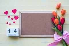 O calendário de madeira consiste o 14 de fevereiro em flores e os corações colocaram de lado a lado com uma cor amarela do fundo  imagens de stock