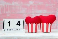 O calendário de madeira o 14 de fevereiro, dois corações vermelhos foi colocado de lado a lado e o fundo é cor-de-rosa Dia do Val imagens de stock royalty free