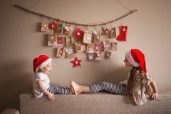 O calendário do advento que pendura na parede surpresas pequenas dos presentes para crianças duas irmãs vestidas como o jogo dos  fotos de stock