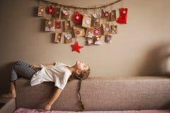 O calendário do advento que pendura na parede surpresas pequenas dos presentes para crianças mentiras e olhares da menina no cale fotografia de stock