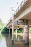 O calibre grande do pessoal estabelece-se ao lado da ponte para a monitoração da água Imagem de Stock Royalty Free