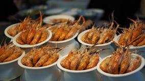 O camarão preparado vermelho delicioso é servido em suas placas Prato do camarão no mercado asiático tradicional do alimento vídeos de arquivo