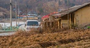 O caminhão branco estacionado ao lado de uma corrida velha abandonou para baixo a barraca com imagem de stock royalty free