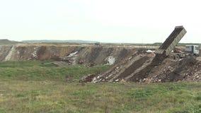 O caminhão com um reboque drapejou o desperdício da construção do tijolo, do concreto e da argila na operação de descarga, onde o filme