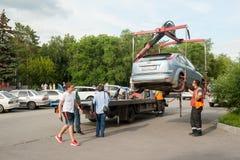 O caminhão de reboque toma o carro estacionado na violação Rússia fotos de stock