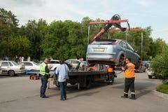 O caminhão de reboque toma o carro estacionado na violação Rússia foto de stock