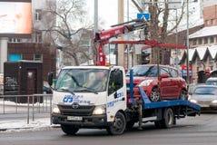 O caminhão de reboque toma o carro estacionado na violação Rússia imagens de stock royalty free