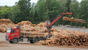 O caminhão de Volvo FH descarrega logs na jarda de madeira serrada Imagens de Stock