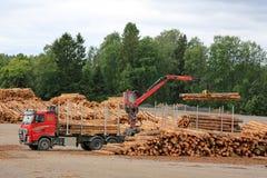 O caminhão de Volvo FH descarrega logs na jarda de madeira serrada Foto de Stock