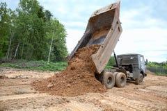 o caminhão do Descarga-corpo descarrega uma terra Imagens de Stock