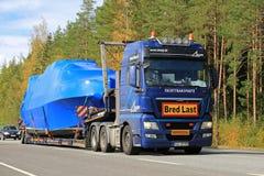O caminhão do HOMEM transporta um barco como a carga excepcional Fotografia de Stock Royalty Free