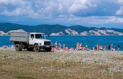 O caminhão na praia que recolhe o lixo foto de stock royalty free