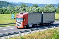 O caminhão vermelho de Scania acoplado com reboque drived na estrada do slovak D1 no campo imagens de stock
