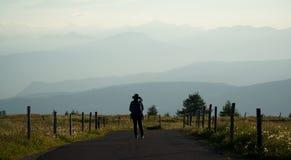 O caminhante aprecia a vista em montanhas da dolomite no por do sol Imagens de Stock