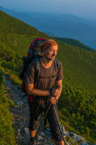 O caminhante com trouxa está descansando e olha o sol de aumentação no mo Fotos de Stock Royalty Free