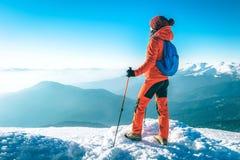 O caminhante com trouxas alcança a cimeira do pico de montanha Liberdade do sucesso e realização da felicidade nas montanhas Engo imagens de stock