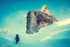 O caminhante com trouxas alcança a cimeira do pico de montanha Liberdade do sucesso e realização da felicidade nas montanhas Engo fotos de stock