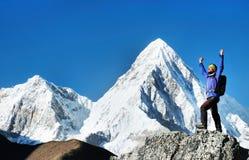 O caminhante com trouxas alcança a cimeira do pico de montanha Liberdade do sucesso e realização da felicidade nas montanhas Espo imagem de stock