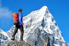 O caminhante com trouxas alcança a cimeira do pico de montanha Liberdade do sucesso e realização da felicidade nas montanhas Espo foto de stock royalty free