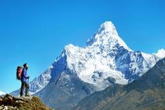 O caminhante com trouxas alcança a cimeira do pico de montanha Liberdade do sucesso e realização da felicidade nas montanhas Espo fotos de stock royalty free