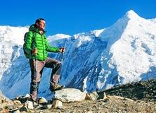 O caminhante com trouxas alcança a cimeira do pico de montanha Liberdade do sucesso e realização da felicidade nas montanhas Espo fotografia de stock royalty free