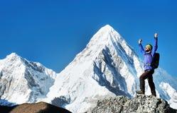 O caminhante com trouxas alcança a cimeira do pico de montanha Liberdade do sucesso e realização da felicidade nas montanhas Espo foto de stock