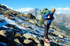 O caminhante com trouxas alcança a cimeira do pico de montanha Liberdade do sucesso e realização da felicidade nas montanhas Espo fotografia de stock