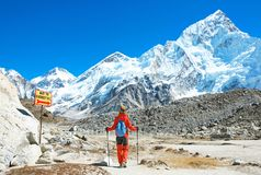 O caminhante com trouxas alcança a cimeira do pico de montanha SuccesHiker com trouxas alcança a cimeira do pico de montanha Suce fotografia de stock