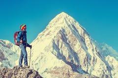 O caminhante com trouxas alcança a cimeira do pico de montanha Sucesso, liberdade e felicidade, realização nas montanhas Esporte  fotografia de stock royalty free