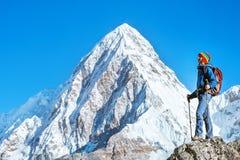 O caminhante com trouxas alcança a cimeira do pico de montanha Sucesso, liberdade e felicidade, realização nas montanhas Esporte  foto de stock